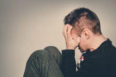 Человек плачет Молодой человек в депрессии сидя на поле держа руки Парень прячет его сторону с его руками Головная боль Спрятать Стоковое Фото