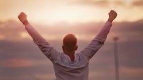 Человек победителя делая рукой повышения жеста выигрыша желтую предпосылку неба захода солнца шарлаха наслаждаясь триумфом видеоматериал