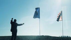 Человек победоносно поднимает его руки на фоне флагов сток-видео
