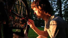 Человек поворачивает колесо на переворачиванном велосипеде, парень ремонтирует спицы на заходе солнца в парке стоковое изображение