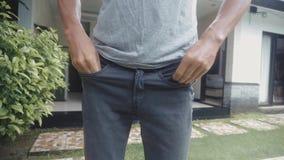 Человек поворачивает пустые карманы его джинсов перед домом изолированные деньги отсутствие детенышей белой женщины видеоматериал