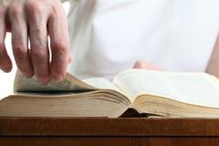 Человек поворачивая страницу библии Стоковая Фотография RF