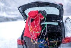Человек подготавливает цепи для автошин на холодный день стоковая фотография rf