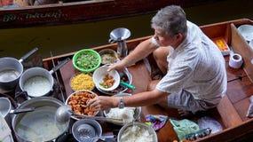 Человек подготавливая еду на рынке Damnoen Saduak плавая около Bangko Стоковое Изображение RF