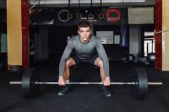 Человек поднимает в баре спортзала, поездах спортсмена, занимаясь культуризмом стоковое фото rf