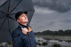 человек под зонтиком прячет от дождя и смотрит к небу, ждать хорошее weather_ Стоковая Фотография RF