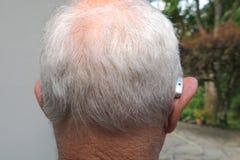 Человек пожилого гражданина нося современный цифровой высокотехнологичный аппарат для тугоухих в взгляде задней части уха стоковая фотография rf