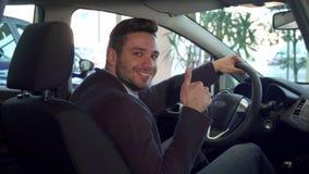 Человек показывает его большой палец руки вверх внутри автомобиля стоковые фотографии rf