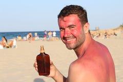 Человек показывая загорая лосьон пока получающ sunburned Стоковое Фото