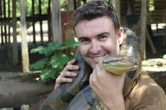 Человек показывая привязанность для исполинской змейки стоковые фотографии rf