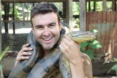 Человек показывая привязанность для исполинской змейки стоковые изображения rf