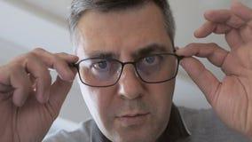 Человек полагаясь вниз во взглядах сюрприза впереди его, принимающ его стекла от его глаз акции видеоматериалы