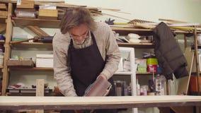 Человек полирует древесину с машиной для молоть видеоматериал