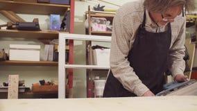 Человек полирует древесину с машиной для молоть акции видеоматериалы