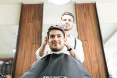 Человек получая волосы уравновешенный от парикмахера в парикмахерской стоковая фотография