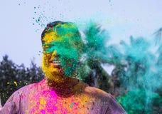 Человек получая политый с цветами holi во время фестиваля holi в Индии стоковое изображение