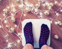 Человек получил вверх на белых электронных масштабах после торжества Нового Года и рождества Стоковые Фото