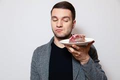 Человек портрета крупного плана молодой милый кавказский держа белую круглую плиту с частью торта печенья, подготавливающ съесть  стоковое изображение