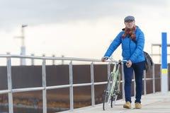 Человек портрета старший идя с его велосипедом в улице стоковые фото