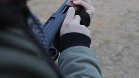 Человек поручает боеприпасы в корокоствольном оружии конец-вверх оружий и его рук видеоматериал