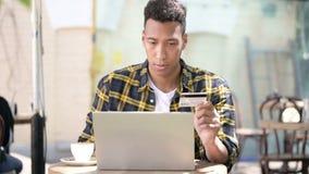 Человек после онлайн ходя по магазинам отказа, на открытом воздухе кафе осадки молодой африканский сток-видео