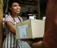 Человек поставляет почтовый ящик к женщине перед стопом стоковые фотографии rf