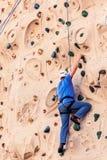 Человек постаретый серединой в голубой взбираясь стене Стоковое Изображение