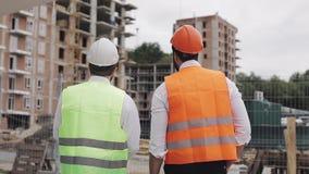 Человек построителя и архитектора обсуждает план строительства современного делового центра стоя близко сток-видео