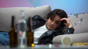 Человек похмелья просыпая вверх в грязной комнате после партии ночи, образа жизни пьяницы бесполезного акции видеоматериалы