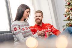 Человек представляя подарок рождества к подруге Стоковые Фотографии RF