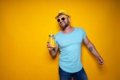 Человек представляя с ярким оранжевым питьем Стоковое Изображение RF