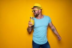 Человек представляя с ярким оранжевым питьем Стоковая Фотография RF
