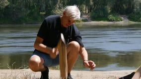 Человек прерывая древесину для огня : Пеший туризм, перемещение, зеленая концепция туризма Здоровый активный образ жизни Река и видеоматериал