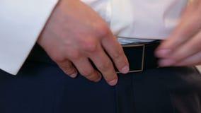 Человек прикрепляет пояс на его брюках, конец-вверх акции видеоматериалы