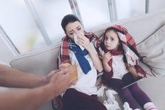 Человек принес его жену и дочь горячий горячий чай Женщина обнимая девушку и дуя ее нос Стоковое Фото