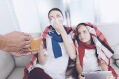 Человек принес его жену и дочь горячий горячий чай Женщина обнимая девушку и дуя ее нос Стоковые Фото