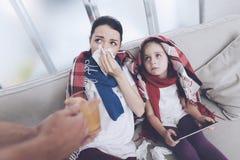 Человек принес его жену и дочь горячий горячий чай Женщина обнимая девушку и дуя ее нос Стоковые Изображения RF