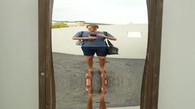 Человек принимает его отражение в ложном зеркале на камере путешествие образа жизни 4K сток-видео