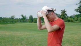 Человек принимает его шлемофон VR от его головы в парке акции видеоматериалы