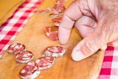Человек принимает кольца копченой сосиски отрезанные для пробовать Стоковые Фото