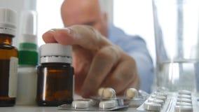 Человек принимает лечение медицины выбирает некоторые таблетки от таблицы стоковое изображение rf