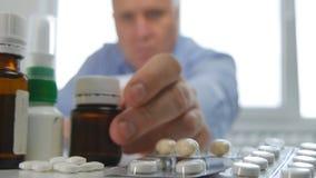 Человек принимает лечение медицины выбирает некоторые таблетки от таблицы стоковое фото