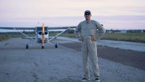 Человек принимает на шляпу, стоя на взлётно-посадочная дорожка Портрет женского пилота акции видеоматериалы