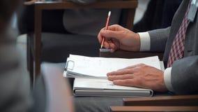 Человек принимает примечания в карандаше в тетради во время конференции акции видеоматериалы