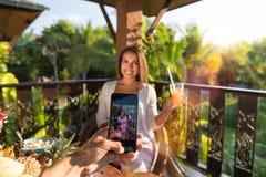 Человек принимает фото женщины с соком на парах телефона клетки умных на завтраке совместно сидя на таблице на террасе лета Стоковое Фото
