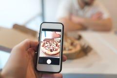 Человек принимает фото коробки пиццы на его сотовом телефоне Фото фаст-фуда на smartphone Стоковые Изображения