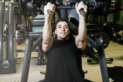 Человек приниманся за имитатору блока в спортзале Стоковая Фотография RF