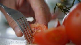 Человек принимая с кусками вилки красных томатов стоковые изображения rf