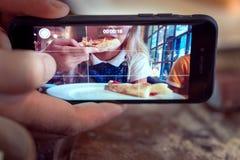 Человек принимая фото девушки есть пиццу стоковые фотографии rf