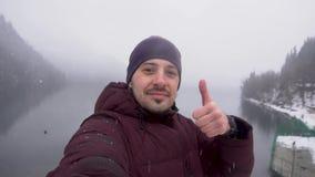 Человек принимая selfie и показывая большой палец руки вверх на озере Ritsa в абхазии в зиме акции видеоматериалы